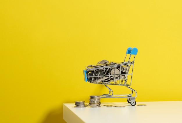 ミニチュアの金属製のショッピングカートと白いテーブルの上のコインのスタック。割引と販売、予算の節約の概念。オンライン取引