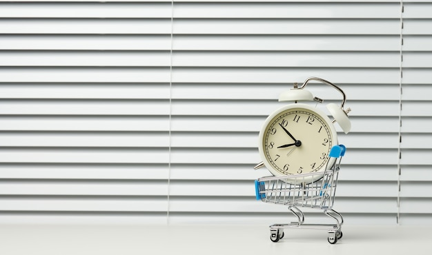 Miniature metal shopping cart on wheels and in the middle of a round alarm clock on a white table. start of discounts, sale, copy space