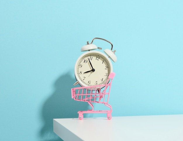 Miniature metal shopping cart on wheels and in the middle of a round alarm clock on a white table. start of discounts, sale