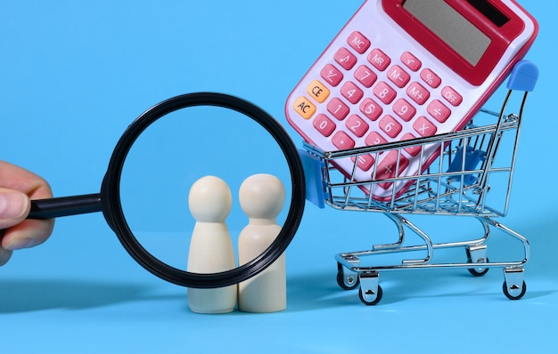 Miniature metal shopping cart with calculator and wooden family. hand with a magnifying glass, the concept of budget control, spending on purchases, saving money