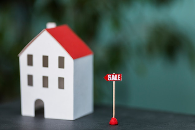 Miniature model of house real estate for sale against blurred backdrop