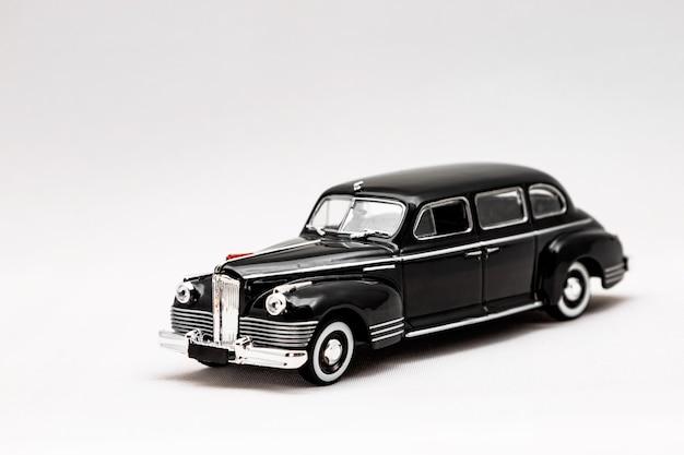 흰색 표면에 레트로 자동차의 미니어처 모델. 장난감 자동차 모형