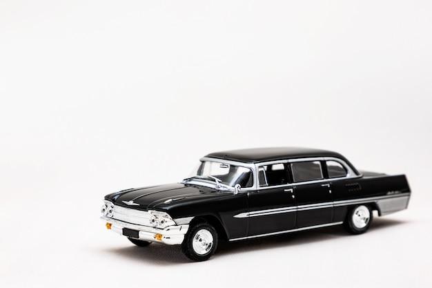 白い表面にレトロな車のミニチュアモデル。おもちゃの車のモデル