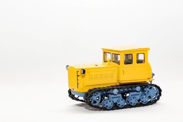白い背景で隔離の黄色のクローラートラクターのおもちゃのミニチュアモデル