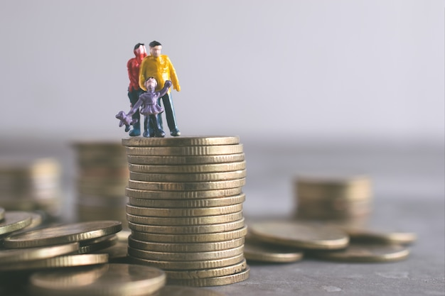 Miniature mum dad and kids standing on top of the money save money concept