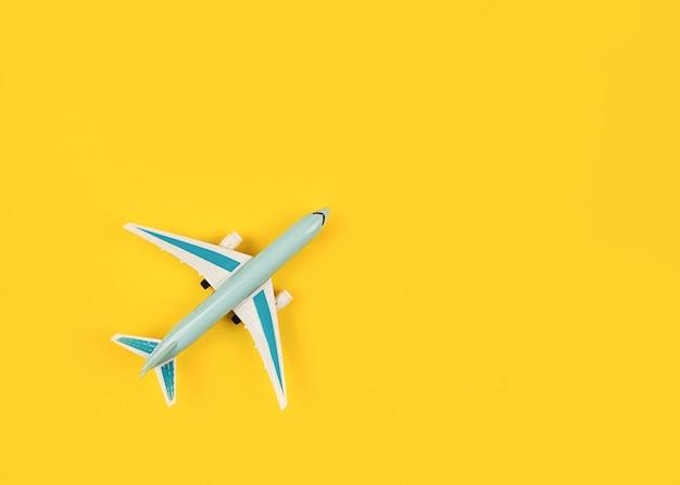 노란색 배경 개념 항공 여행 티켓 예약에 파란색 비행기의 미니어처
