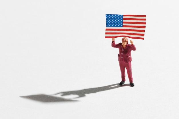 Миниатюра женщины, держащей над головой американский флаг. концепция сторонника патриота или политической кампании. маленькая миниатюрная фигура стоя изолирована