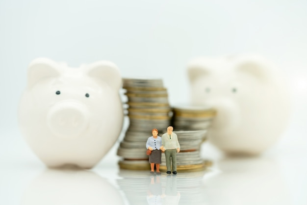 Miniature of old people standing with coins stack and piggy bank