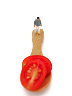Miniature ole man standing on fresh grape or cherry tomato with wooden spoon on white back
