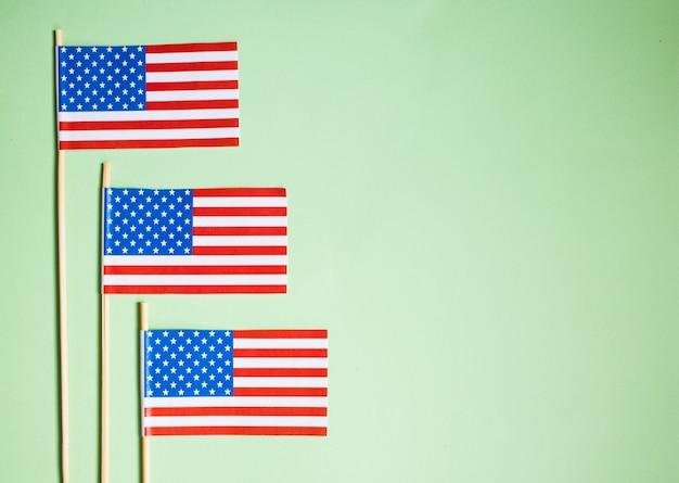 Миниатюрный бумажный флаг сша. американский флаг на зеленом фоне.