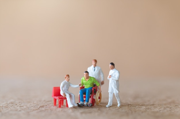 Miniature patient in wheelchair consulting with doctors on light background