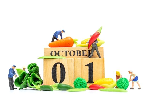 흰색 바탕에 나무 달력 10월 1일 작업 미니어처 사람들 농업. 세계 채식주의의 날 개념