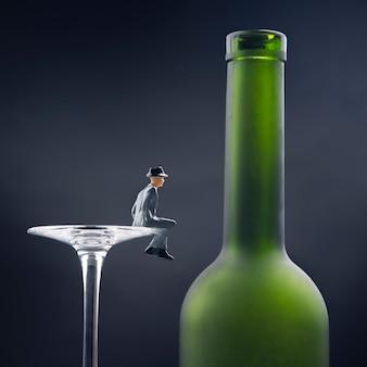 ミニチュアの人々。アルコール依存症の問題の概念。アルコール依存症の人は、ボトルの近くのワイングラスの端に座っています