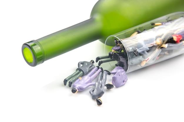 미니어처 사람들. 알코올 중독 문제 개념입니다. 알코올 중독자는 병의 배경에 대해 와인 잔에 있습니다.