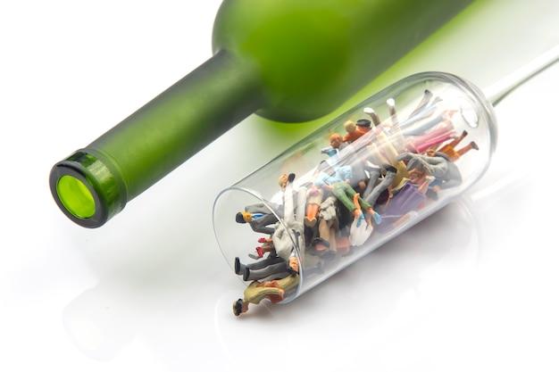 ミニチュアの人々。アルコール依存症の問題の概念。アルコール依存症は、ボトルを背景にワイングラスに入っています。