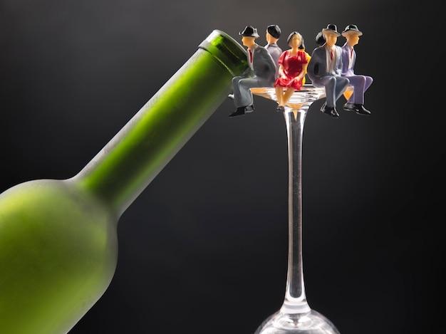 ミニチュアの人々。アルコール依存症の問題の概念。アルコール依存症はワイングラスに入っています