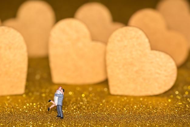 Миниатюрные люди и золотые сердечки. влюбленная пара на сияющем фоне.