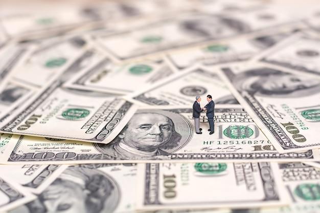 ミニチュアの人々とお金。取引の創造的な概念。 2人のビジネスマンが握手します。