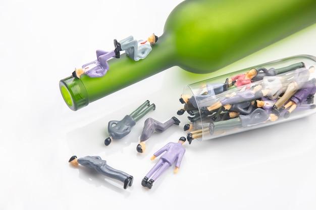 ミニチュアの人々は、白い背景にワイングラスの底にいるアルコール依存症です