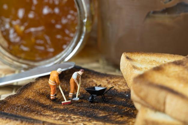 ミニチュアの人々は焦げたトーストを掃除しています。