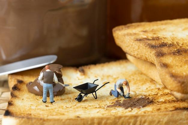 ミニチュアの人々がトーストにチョコレートを広げています。