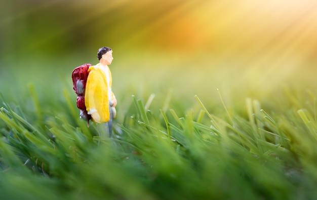Миниатюрные люди, рюкзак путешественника утренняя прогулка на фоне зеленого луга на природе