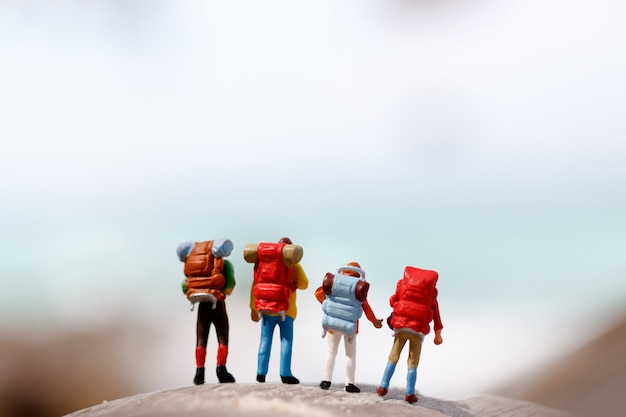 Miniature people: backpacker celebrating success standing on top at the peak of a mountain.