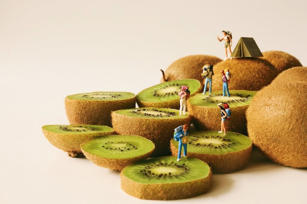 Miniature people backpacker on fresh kiwi.