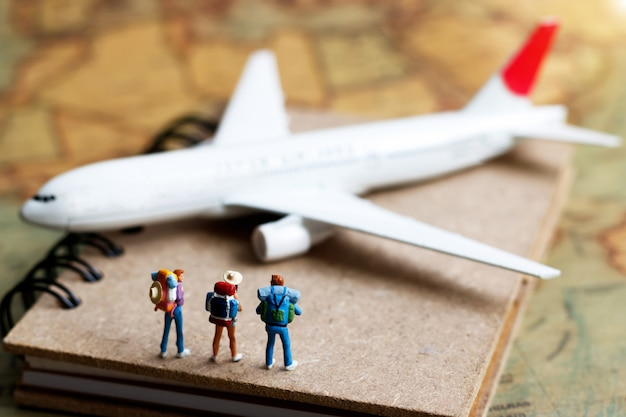 Miniature people, backpacker standing on book with airplane.