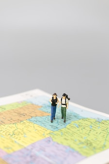지도 여행 및 모험 개념에 걷는 미니어처 사람들 배낭.