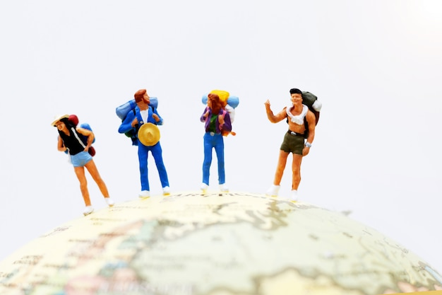 Miniature people, backpackers on the globe walking to destination.