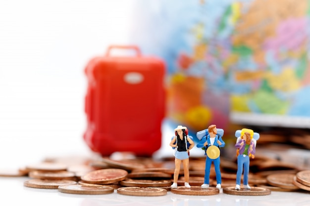 Miniature people, backpackers standing on stack of coins with globe and bag.
