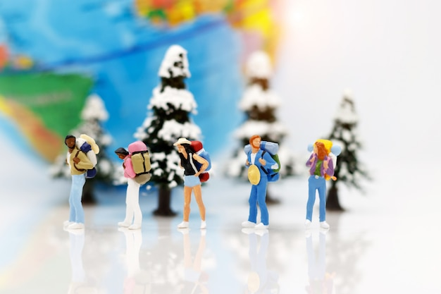 Miniature people, backpackers with globe walking to destination. travel concept.