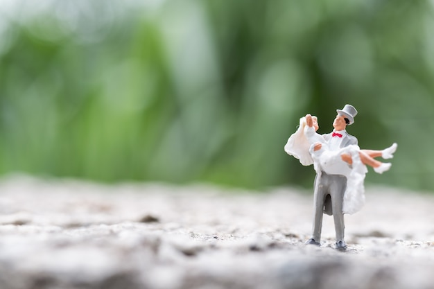Miniature people:  bride and groom couple standing outdoor
