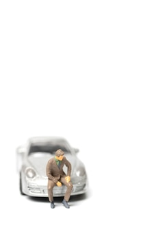車に座ってテキストのスペースをコピーするミニチュアの人々のビジネスマン