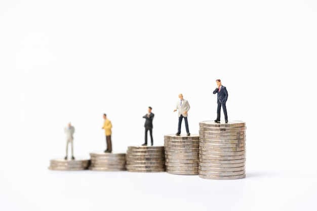 Miniature people, business man standing on stack of coins.