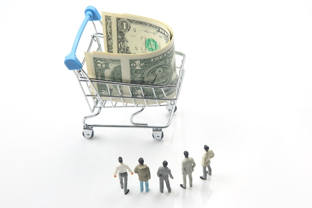 Miniature people. business men stand near dollar money in a grocery basket. business entrepreneur concept