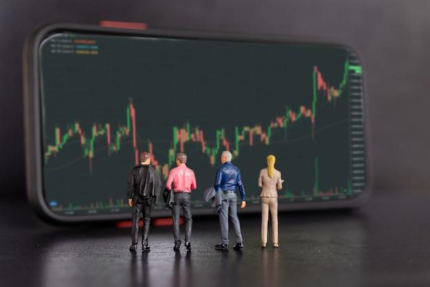 Миниатюрные люди, деловые люди и смартфон с тикерами акций, графиком фондовой биржи или форекс в графической концепции