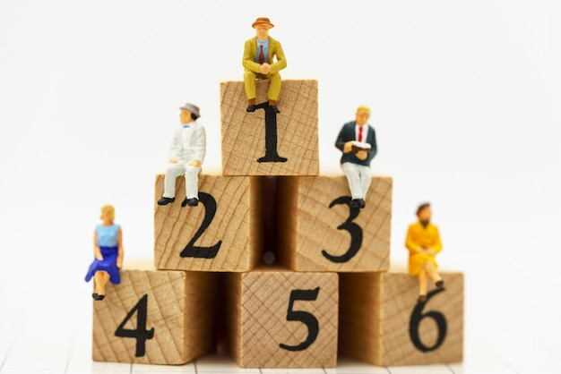 Miniature people: business people sitting on wooden box step.