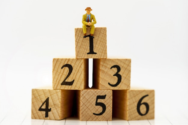 Miniature people: business people sitting on wooden box with number