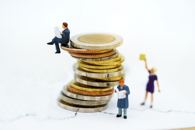 Miniature people: business team reading book  on coins stack.