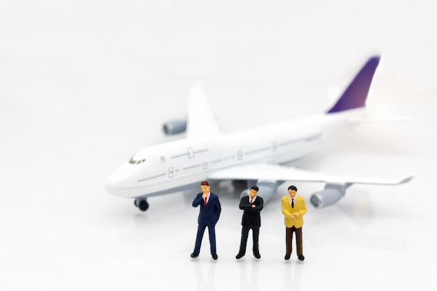 Miniature people: business team standing in front of airplane. business concept.