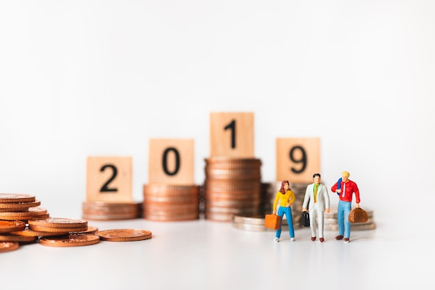 Miniature people, business team standing with golden stack coins and year 2019