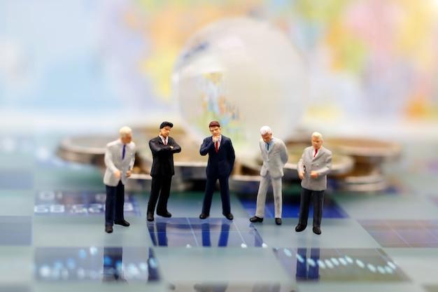 Миниатюрные люди, бизнесмен думает с глобусом на стеке монет. концепция стратегии с мышлением.