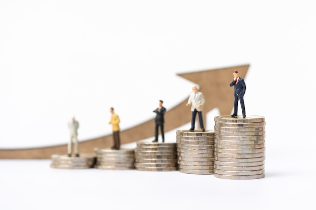 Miniature people, businessman on coins stack with arrow wooden icon.