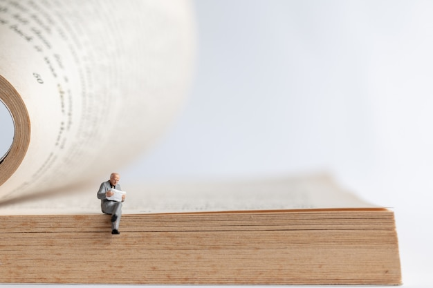 Miniature people: businessman reading book on  old book