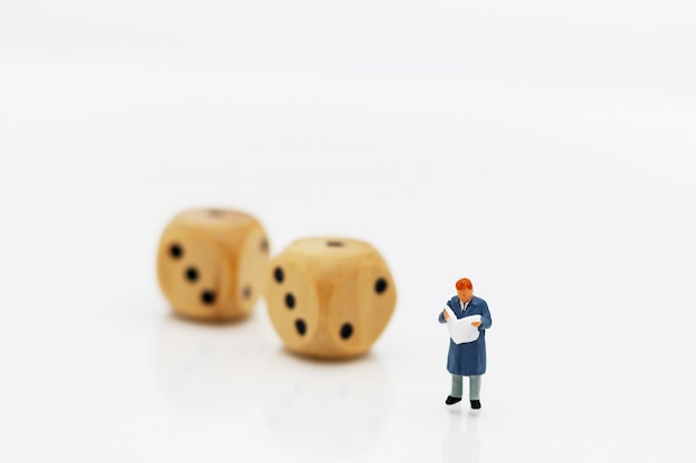 Miniature people: businessman reading book with dice.