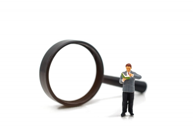 Miniature people: businessman reading book with magnifier.
