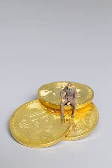 Miniature people businessman sitting on  bitcoin coins , future investment concept