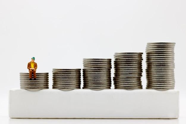 ミニチュアの人々:コインのお金のステップに座っているビジネスマン。金融とお金の概念。